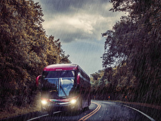 Bus driving on a road under a heavy rain with headlights on.