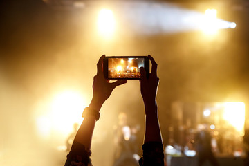 Silhouette of man taking pictures with his smartphone on music show
