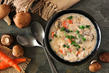 Creamy mushroom soup. Autumn food concept. Above view scene on a dark slate background.