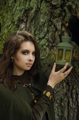 young woman in a Halloween witch costume and with a bright make-up near the mossy trunk of an old tree