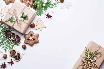 Christmas and New Year celebration traditions concept. Composition of festive decorations, gingerbread cookies and gift box on white background with copy space for text design