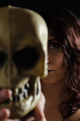 Portrait of a girl holding a skull in front of her.