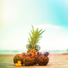 Pineapple and Coconuts Wearing Sunglasses On Carribean Beach