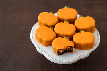 White platter with small orange frosted pumpkin cakes, one with bite taken out, on brown background