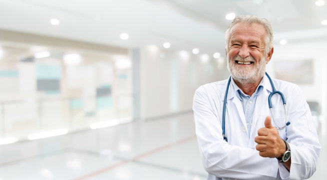 Happy senior doctor standing in the hospital.