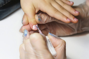 Professional manicure for child. Cosmetologist applies healing and firming varnish on nails on child's fingers. Shooting close-up.