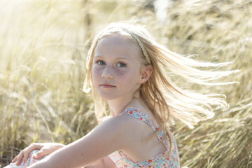 Beautiful Innocent Little Girl With Blue Eyes, Blond Hair and Freckles in the Sun on a Windy Day