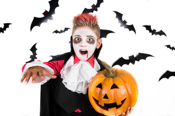 Scary Halloween vampire boy dressed up for spooky halloween party and holding an orange halloween pumpkin jack o lantern