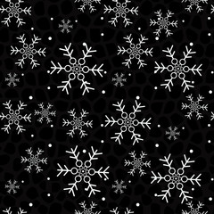 Snowflakes on a black background. Christmas seamless background.