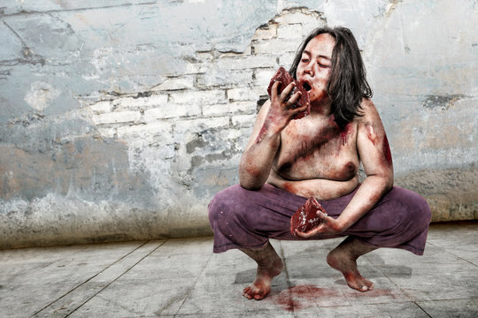 Spooky zombie man eating bloody meat