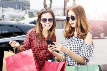 Beautiful two asian woman in sunglasses looking at the phone while carrying shopping bags