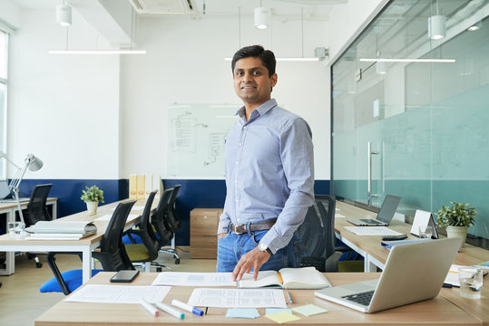 Portrait of happy Indian UX designer standing in modern office
