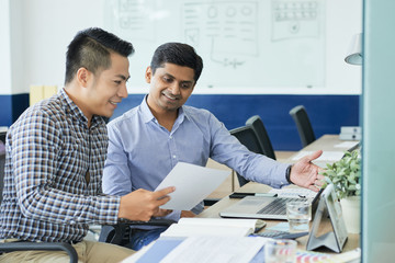 Vietnamese UX designer showing his ideas to Indian coworker