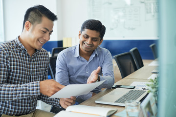 Cheerful multi-ethnic coworkers discussing document at business meeting in office