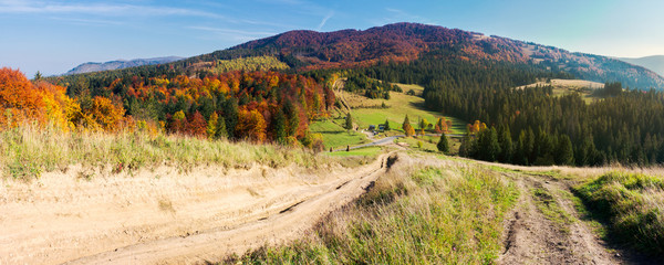 panorama of mountainous landscape in autumn. country road down the hill. parking lot in the valley. forest in fall colors