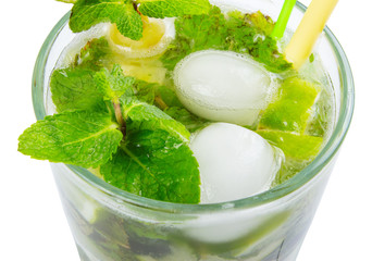 non alcohol mojito with ice, mint and lime in a tall glass. closeup view from the top isolated on a white background