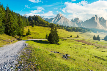 country road winds through the valley. mountains with high rocky peaks in the distance. composite image of a beautiful landscape at hazy sunrise
