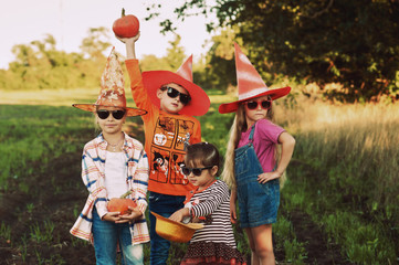 Halloween . Funny kids in with pumpkins in nature