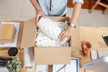 Small business owner packing vase to send it to customer, view from above