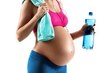 Resting time. Close up of pregnant woman in sportswear holding towel and bottle of water isolated on white background. Concept of healthy life