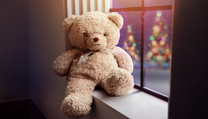 Lonely Teddy Bear Sitting nearby Window in House on Christmas Night, Xmas Tree with Lights as outside view