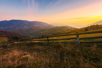 beautiful sunrise in mountains. wonderful countryside scenery in autumn. fence along the rural fields. fog in the distant valley