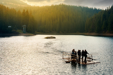 Synevir, Ukraine - OCT 20, 2008: group of young tourists on a wooden raft in the middle of a lake. gorgeous evening light above the forest on hill in the distance. wonderful atmosphere of autumn