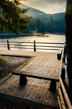 Synevir, Ukraine - OCT 20, 2008: wooden bench on the pier of a Synevyr lake. beautiful autumn evening