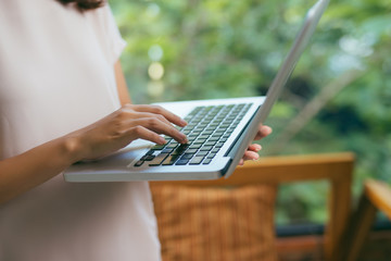 Portrait of young woman working holding laptop standing against panoramic window with garden view