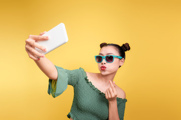 Carefree and happy, funky mood. Attractive asian woman taking selfies with smile.