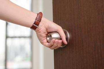 Close-up hand holding door knob, opening door slightly, selective focus
