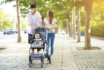 happy family with baby carriage walking in the park