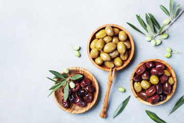Olives in wooden bowls decorated with fresh olive tree branch top view.