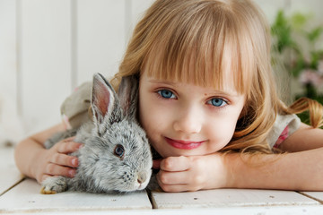 Cute girl hugging with rabbit while lying on the floor at home