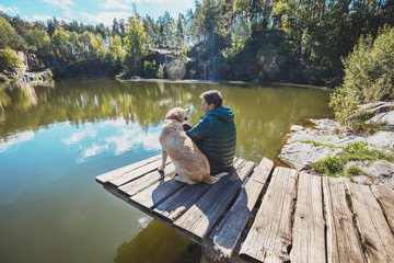 A man with a Labrador retriever dog sits on a wooden deck on a beautiful rocky shore of a lake and looks at the water