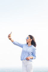 Lovely woman holding a smartphone and takes a selfie, looks with a smile at the camera against the white sky on the street,