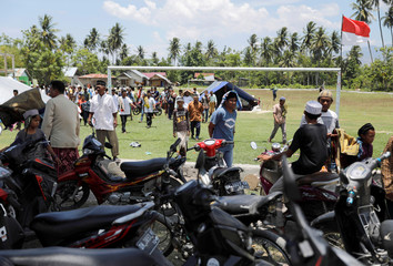 Residents walk after attending Friday prayers in a soccer stadium at Lolu village outside Palu
