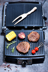 Wall Mural - Beef steaks and vegetables on electric grill