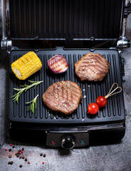 Fototapete - Beef steaks and vegetables on electric grill