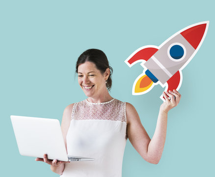 Woman holding a rocket and using a laptop