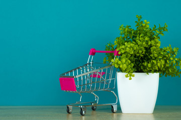 Shopping cart or supermarket trolley with little decoration tree on table with copy space for business finance shopping and marketing concept.