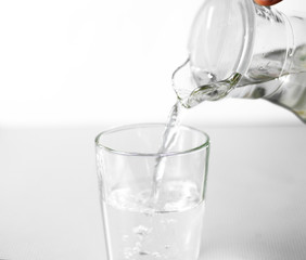 Hand pours water into a glass glass Cup from a glass jug. Close up. Isolated on white background
