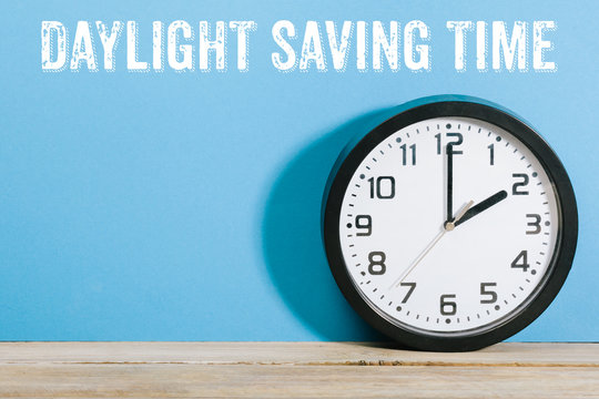 Clock on table with Daylight Saving Time message
