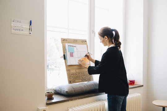 Confident businesswoman writing strategy on placard over window sill at creative office
