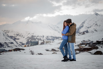 Young lovers on the winter vacations spending time in mountains