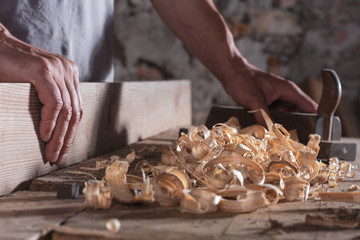Man scraping curled wood scraps with hand plane tool