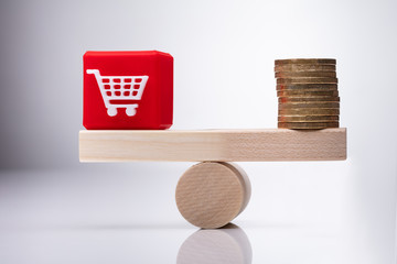 Shopping Cart Cubic Block And Coins Balancing On Seesaw