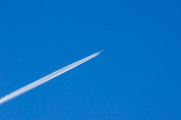 Large passenger supersonic plane flying high in clear blue sky, leaving long white trail