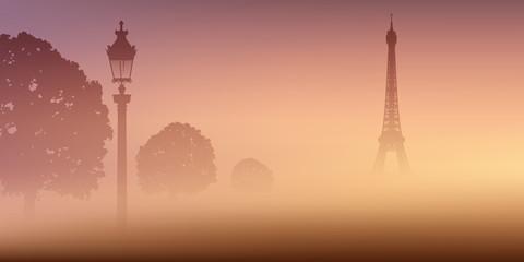 Vue de Paris avec la Tour Eiffel dans la brume au milieu du Champ de Mars, dans la fraîcheur du matin.