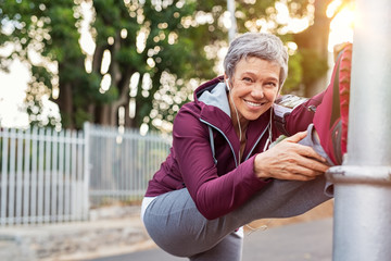 Mature woman warming up before jogging Wall mural
